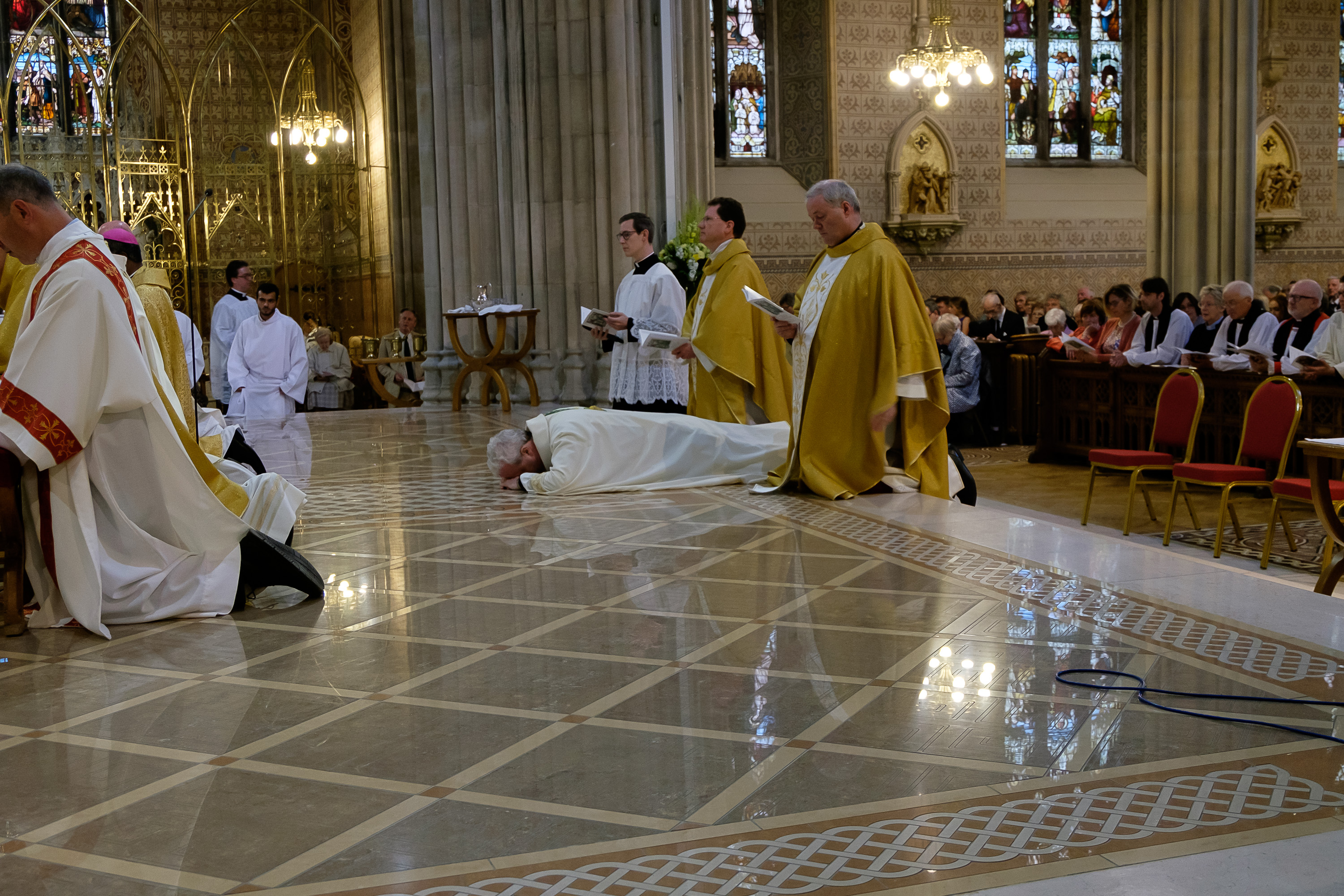 Bishop Michael Router prostrates himself in front of the altar.